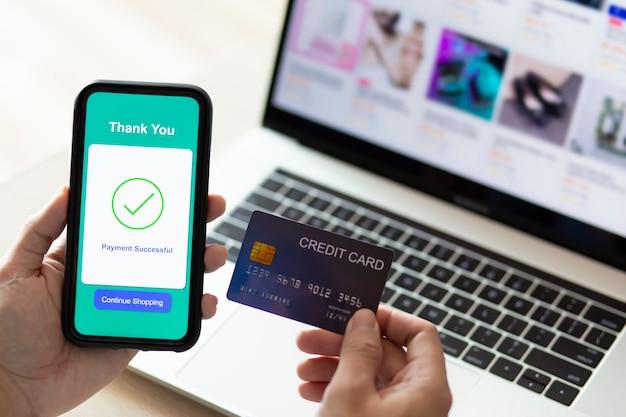 Mains à l'aide d'un téléphone et d'une carte de crédit pour le paiement en ligne