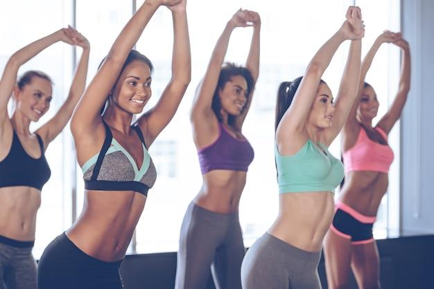 Les mains en l'air! jeunes belles femmes gaies avec des corps parfaits en tenue de sport faisant des étirements avec le sourire tout en se tenant devant la fenêtre au gymnase