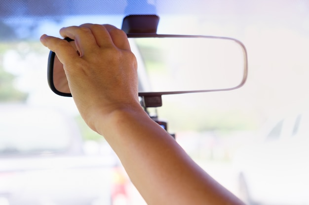 Les mains ajustent le rétroviseur pour un bon freinage et une voiture sûre