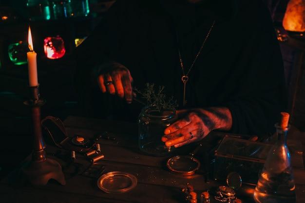 Les mains de l'alchimiste sorcier préparent un poison de potion magique avec des herbes dans un flacon à table