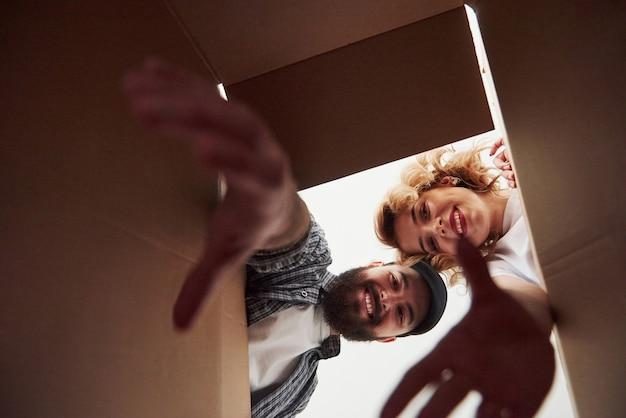 Avec des mains allongées. heureux couple ensemble dans leur nouvelle maison. conception du déménagement