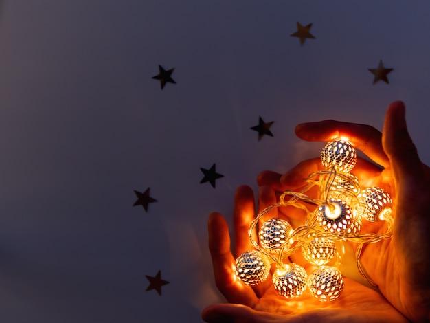 Mains avec des ampoules en forme de coeur. les ampoules métalliques brillent dans le noir.