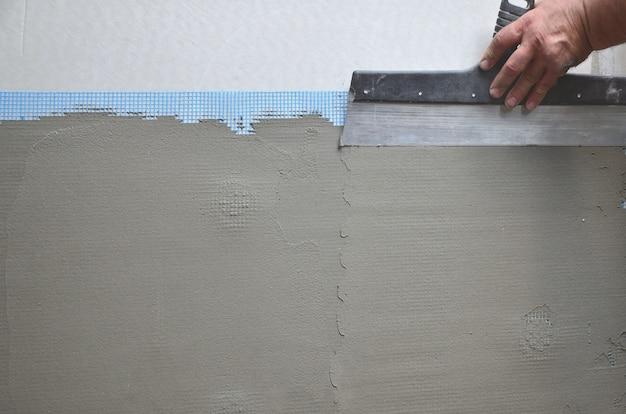 Mains d'un ancien travailleur manuel avec outils de plâtrage mur rénovant la maison