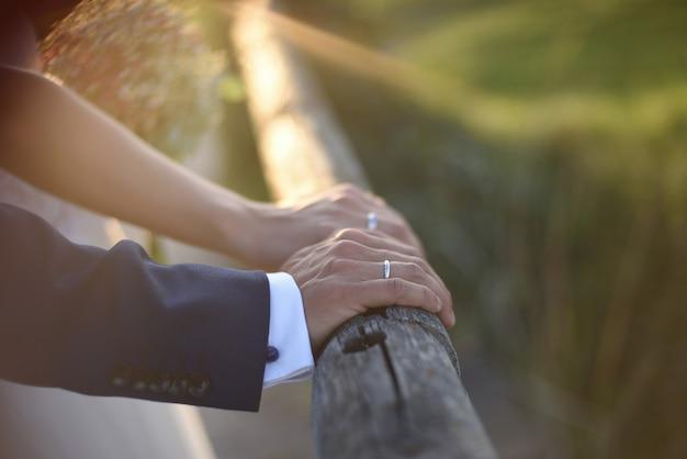 Mains avec anneaux de mariage du couple de jeunes mariés au coucher du soleil