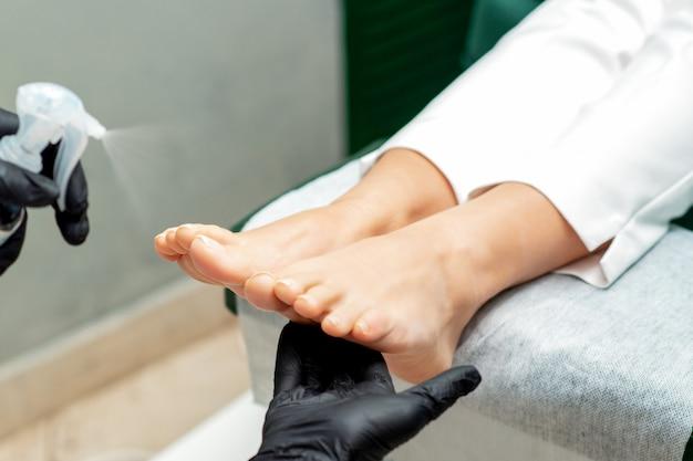 Les mains appliquent un spray sur les pieds
