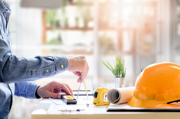 Mains d'architecte travaillant sur blueprint avec des outils de dessin au bureau.