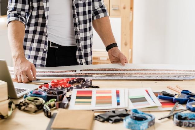 Mains d'artisan contemporain debout par table et en choisissant un élément de décoration pour le nouveau collier pour animaux de compagnie fait main