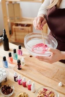 Mains d'artisan mélangeant masse de savon liquide avec couleur cramoisie en verrerie avec bâton en bois sur table