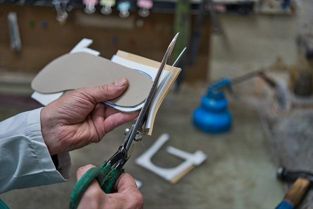 Mains d'un artisan orthopédique coupant des ciseaux avec des modèles en mousse et des artisans en caoutchouc et personnalisées pour les pieds.