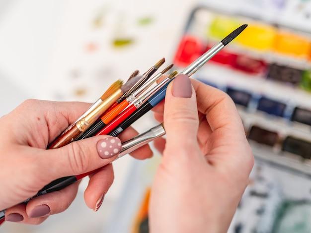 Les mains de l'artiste avec différentes tailles et couleurs pinceaux vue rapprochée avec aquarelle sur
