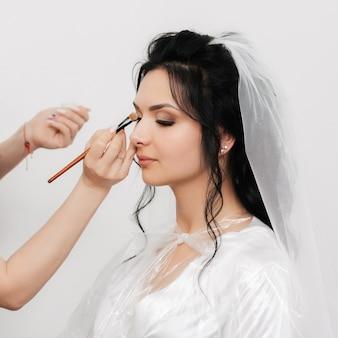 Les mains de l'artiste maquilleur avec un pinceau composent et appliquent des ombres sur les yeux de la jeune fille des mariées dans le salon de beauté