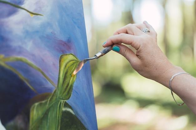 Les mains de l'artiste peignant son travail en plein air.