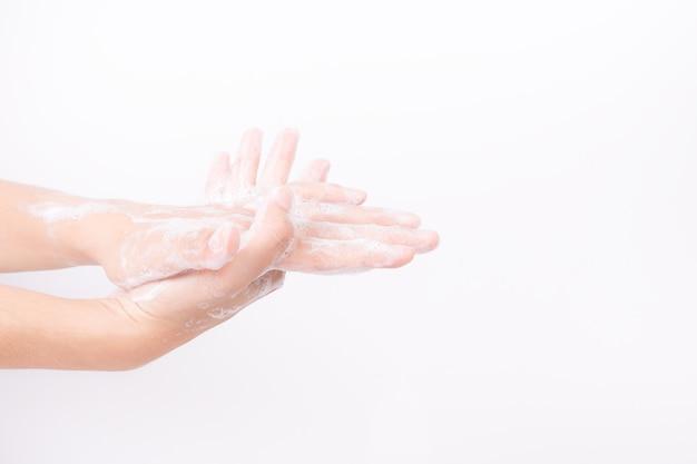 Mains asiat se laver avec des bulles de savon sur fond blanc