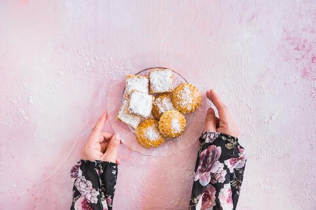 Mains avec assiette pleine de bonbons