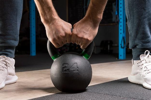 Les mains de l'athlète tenant un poids lourd.