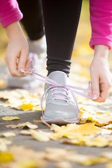 Mains attachant des chaussures aux chaussures sur le pavé d'automne