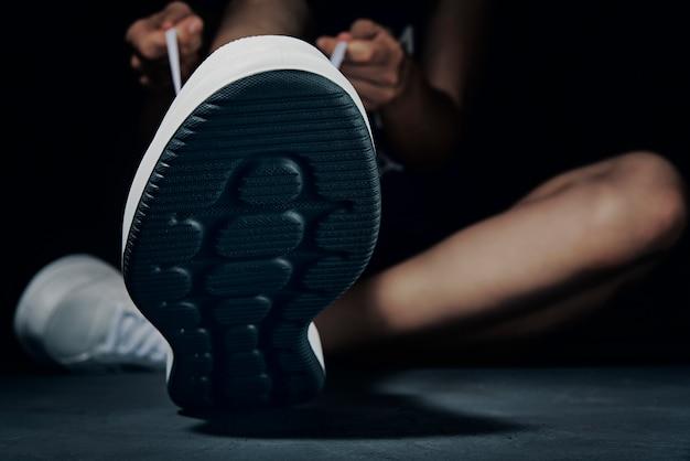 Mains attachant les lacets sur des baskets sur un fond sombre