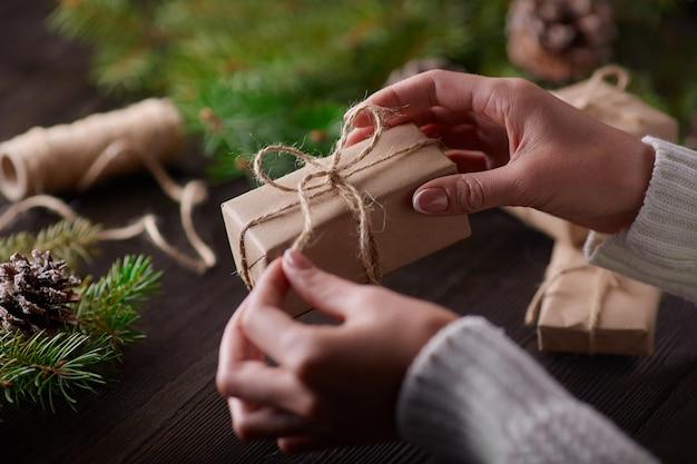 Mains attachant le noeud de chaîne de paquets cadeaux