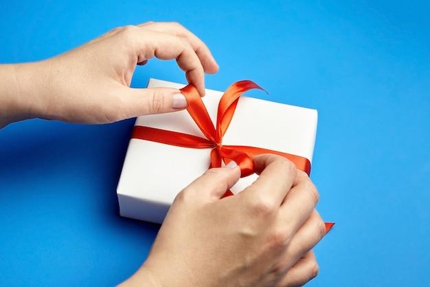 Mains attachant un ruban rouge sur une boîte cadeau blanche sur bleu
