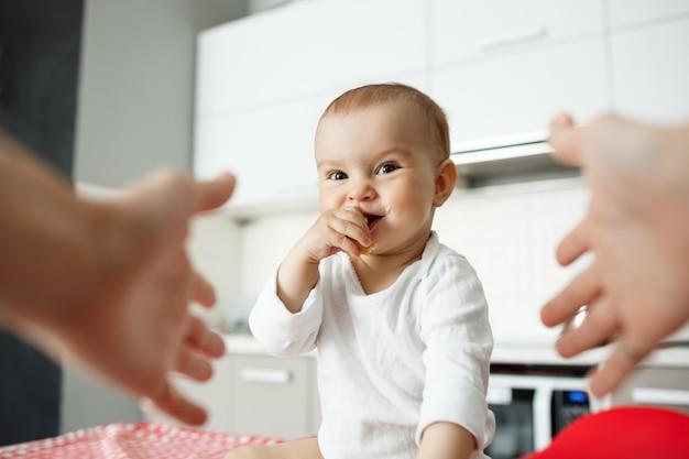 Mains atteignant pour tenir mignon bébé souriant