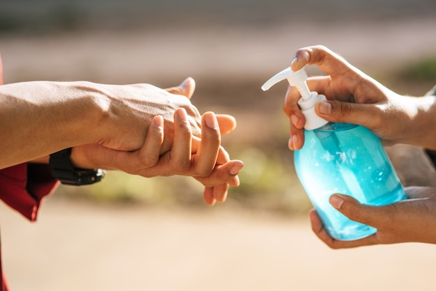 Mains au flacon de gel pour se laver les mains et presser pour que les autres se lavent les mains.