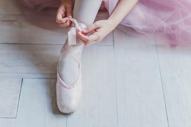 Les mains de la ballerine met des chaussures de pointe sur la jambe