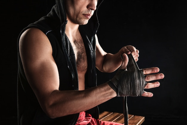 Les mains avec un bandage de kickboxing formation homme musclé sur fond noir