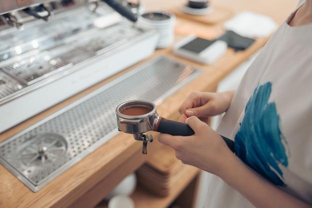 Mains de barista féminin tenant un porte-filtre avec du café moulu frais