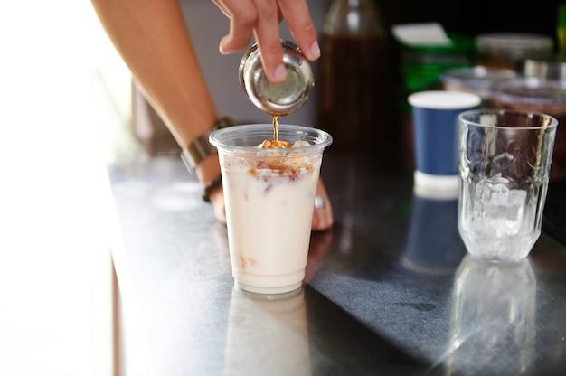 Mains de barista versant une sauce au caramel dans un milk-shake fouetté pour préparer une boisson froide rafraîchissante sur un comptoir de bar