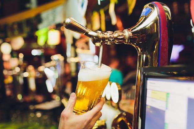 Mains de barman versant une bière blonde dans un verre.
