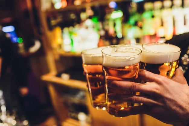 Des mains de barman versent une bière blonde dans un verre.