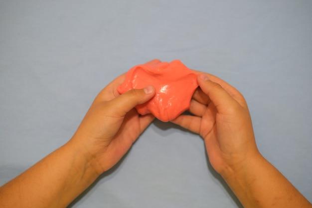 Les mains de bébé se bouchent sur un fond gris, l'enfant joue avec de la pâte à modeler douce