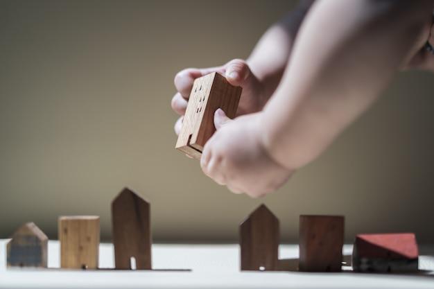 Mains de bébé tenant un modèle de maison. le concept de délocalisation, hypothèque, héritage,