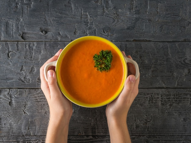 Les mains de bébé tiennent un pot de soupe à la crème fraîche sur une table en bois. soupe du régime végétarien. mise à plat. la vue du haut.