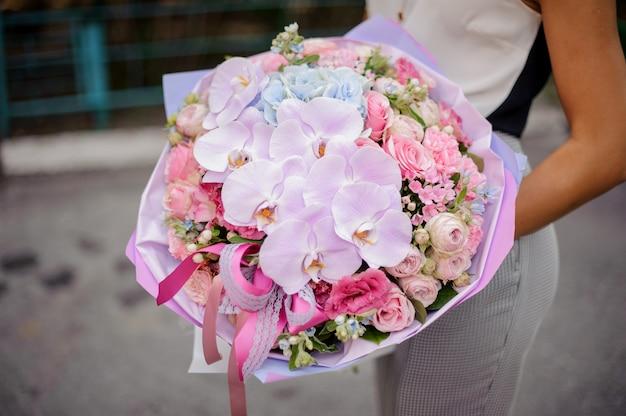 Mains avec une belle et douce composition de fleurs roses