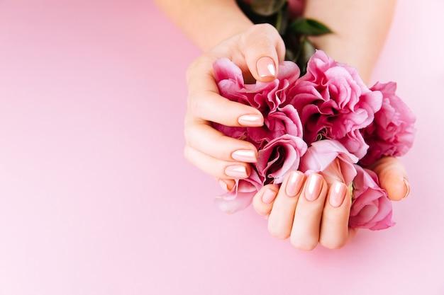 Mains de belle femme avec eustoma frais. concept de spa et de manucure. mains féminines avec manucure rose. concept de soins de la peau douce. ongles de beauté. sur fond beige