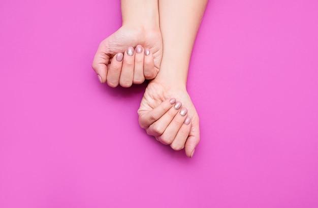 Les mains de la belle femme sur le fond rose. des mains féminines bien entretenues avec une belle manucure dans des tons nude.