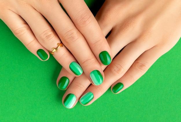 Les mains de la belle femme soignée avec la conception des ongles verts sur la surface verte