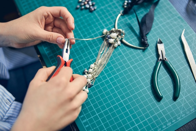 Mains d'un bijoutier qualifié en train de fabriquer un collier à la mode en utilisant une pince à bec rond