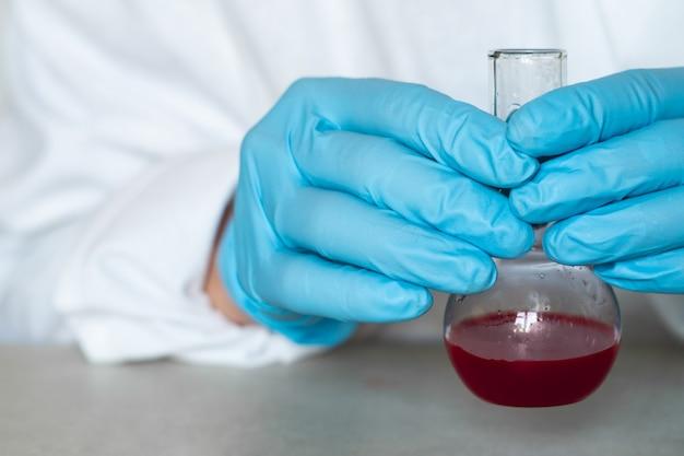 Mains de biochimiste ou virologue tenant un flacon avec un échantillon de sang dans un laboratoire. fermer