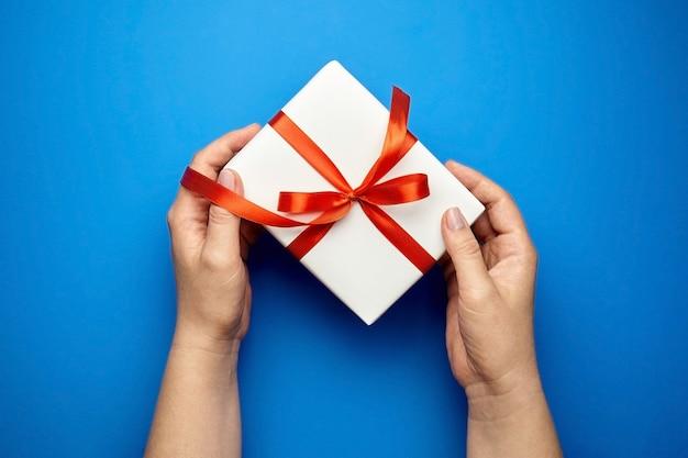 Mains avec boîte-cadeau blanche à égalité avec ruban rouge sur bleu