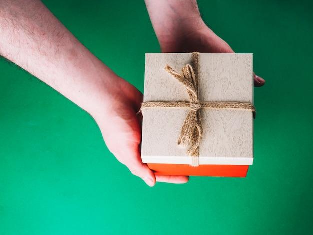 Mains avec boîte-cadeau sur vert