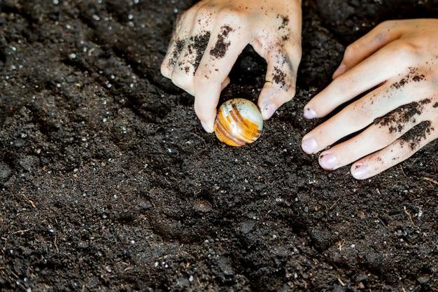 Des mains boueuses sales et un joyau dans le sol