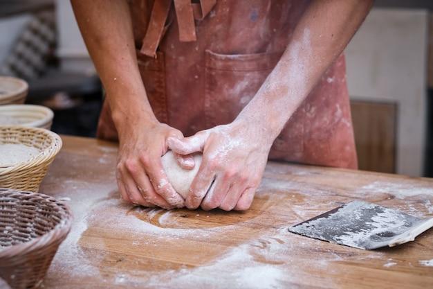 Mains de boulangers masculins travaillant la pâte à pain avec de la farine sur une table en bois