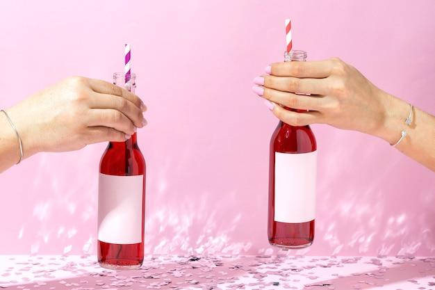 Mains avec des bouteilles et des pailles se bouchent