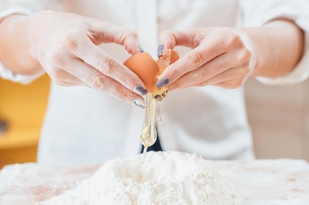 Mains brisant l'oeuf de poule en farine sur la table