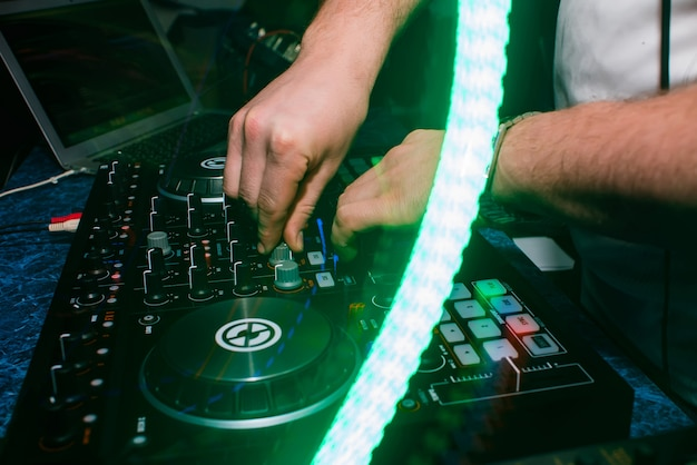 Mains de la cabine de dj jouant de la musique et mixeur en boîte de nuit