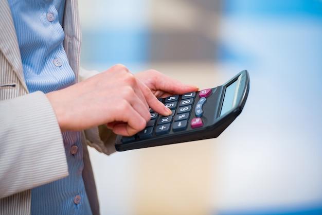 Mains calculant le profit sur la calculatrice