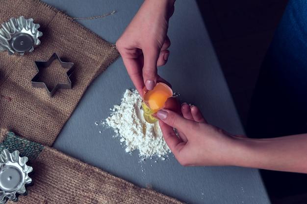 Les mains cassent un œuf de poule en farine