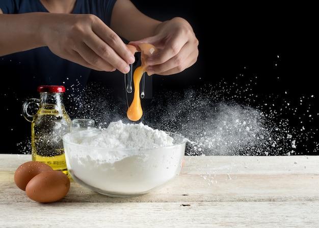 Mains casser un oeuf avec de la farine de vol sur le bois de table